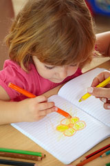 preschooler coloring a picture in a notebook